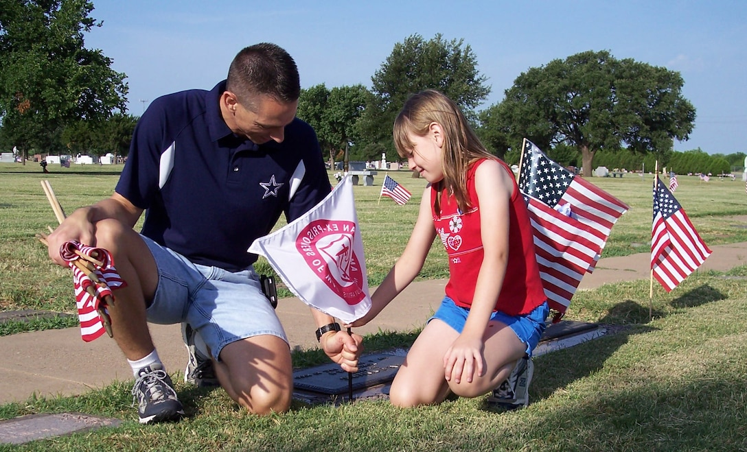 Local Chapter 1054, Air Force Sergeants Association and Sheppard personnel took part in placing American flags on the grave sites of veterans. In this particular photo, AFSA helped place 25 American Ex-Prisoners of War flags.  Master Sgt. Kenneth Boteler, an AFSA member assigned to the 361st Training Squadron, and his daughter are placing one of the 25 American Ex-Prisoners of War flags. The groups place more than 3,000 American flags and 25 American Ex-Prisoners of War Flags. (U.S. Air Force photo).