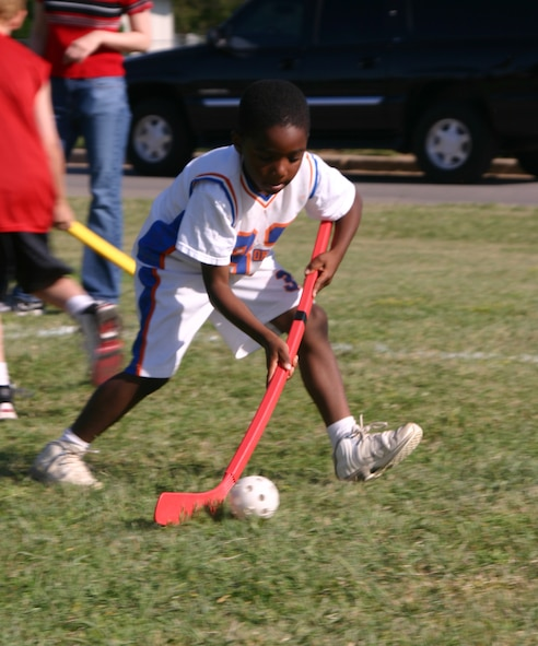 Damante Cross, a first-grade student at Sheppard Elementary, guides the ball during the field hockey race Friday.  (U.S. Air Force photo/Airman Jacob Corbin).