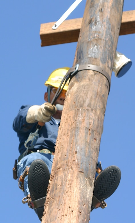 Pole jockeys competing in the Fourth Annual Lineman's Rodeo May 20 had to complete the egg climb as quickly and safely as possible without breaking the egg they carried in their mouth. Above, Airman 1st Class Jose Rodriguez of the 366th Training Squadron prepares to go down a utility pole during the timed event. (U.S. Air Force photo/Senior Airman Tonnette Thompson).