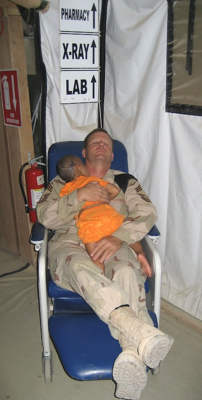 Chief Master Sgt. John Gebhardt cradles a young Iraqi girl as they both sleep in the hospital. The girl's entire family was executed by insurgents. The killers shot her in the head but she survived. The girl received treatment at the U.S. military hospital in Balad, but cries often. According to nurses at the facility, Chief Gebhardt is the only one who can calm down the girl, so he holds her at night while they both sleep in a chair. Chief Gebhardt was assigned to the 332nd Expeditionary Medical Group at Balad Air Base, Iraq. (Courtesy Photo)