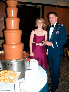 Capt. John V. Brennan, 349th Aircraft Maintenance Squadron, Maintenance Officer, and his guest, Carrie B. Fletcher enjoy a flowing fountain of Belgium chocolate and treats at the 349th Annual Awards Ball, Oct. 21.