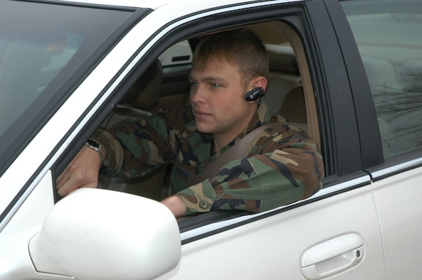 Airman Colin Deuse, 90th Space Wing Safety, demonstrates proper use of hands-free cell phone while driving on base. Hand-held cell phones are not allowed to be used while driving on any DoD installation unless the car is safely parked.