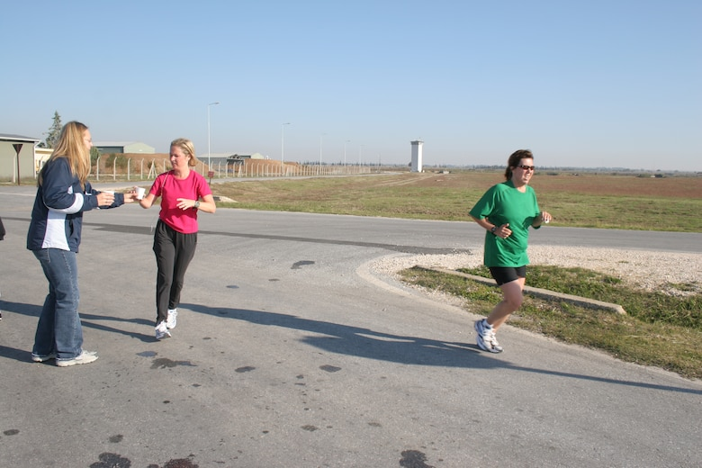 Nicole Kulas (green shirt) and Emily Ozgul (pink shirt) run past the water station by Arkadas Park during Incirlik's first half marathon Nov. 18. Both women have been training for the half marathon for more than nine weeks. This is Mrs. Kulas' fourth half marathon and Mrs. Ozgul's first. They finished just over two hours.
