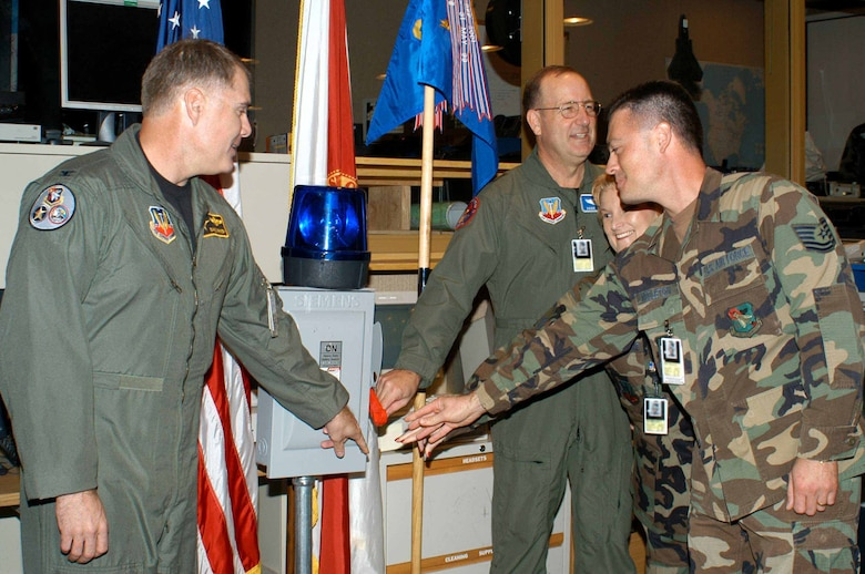 Colonel David Kriner (left) 601 AOC commander, flips the ceremonial switch with (right) Maj. Gen. Hank Morrow, 1st Air Force commander, and SEADS Master Sgt Judy Butler-McGuire and Tech Sgt James Middleton. The ceremony marked the closure of operations at SEADS and its continued transition to the 601st Air Operations Center. (Photo by Deb Kiser)