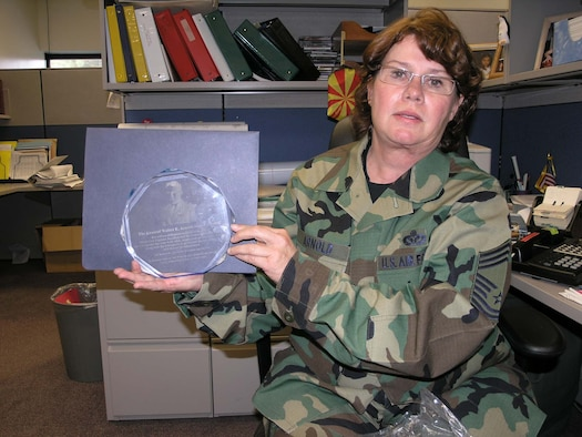 PETERON AIR FORCE BASE, Colo. (AFRC) -- Chief Master Sgt. Sally Arnold shows the award named in her father's honor.  (U.S. Air Force photo by Tech. Sgt. David D. Morton)