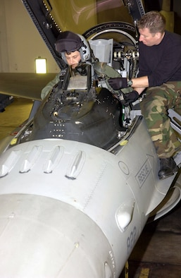 Lt. Col. Andrew Dembosky climbs into his F-16 Fighting Falcon for a mission with the 14th Fighter Squadron at Misawa Air Base, Japan, as Staff Sgt. Robert Parsons helps with preflight preparations.  The 14th FS is preparing to deploy to Iraq.  Colonel Dembosky is the inspector general for Misawa's 35th Fighter Wing.  (U.S. Air Force photo/Senior Airman Robert Barnett)