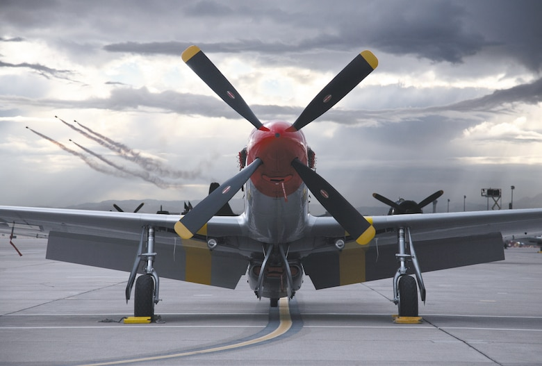 A vintage P-51 Mustang sits on the flightline while the U.S. Air Force Thunderbirds aerial demonstration team peforms during the Nellis Air Force Base, Nev., air show Nov. 11-12, 2006. More than 100,00 people attended the event. (U.S. Air Force photo/Lawrence Crespo)