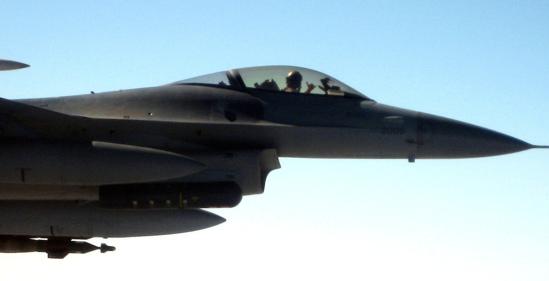 An F-16 Fighting Falcon pilot from Balad Air Base, Iraq, offers the hang loose sign before receiving fuel over Iraq from a KC-10 Extender assigned to the 380th Air Expeditionary Wing Nov. 20. The KC-10 refueled two jets that afternoon in support of Operation Iraqi Freedom. (U.S. Air Force photo/Capt. Justin T. Watson)