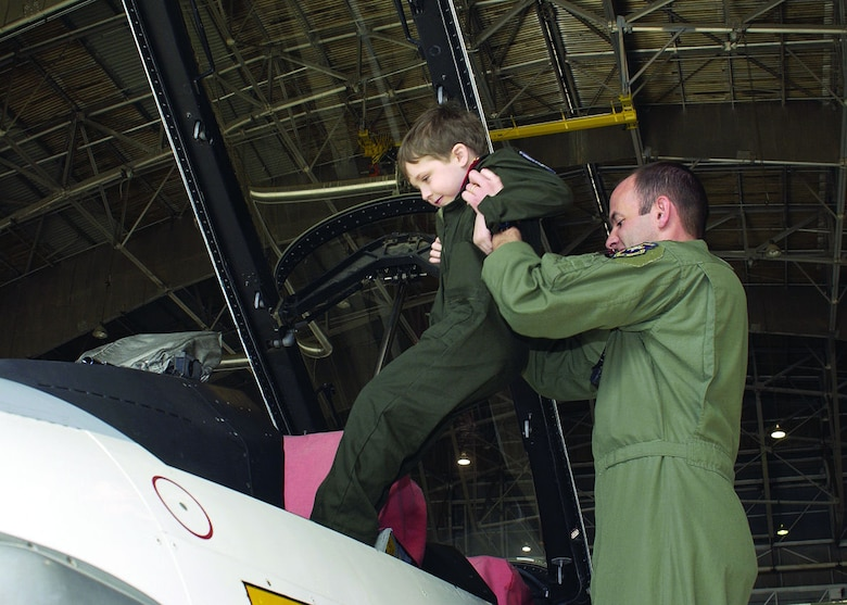 Maj. John Teichert, 411th Flight Test Squadron assistant operations officer, lifts Reilly Koyl, age 5, into an F-16 as part of the Pilot for a Day program. (Photo by Mark McCoy)