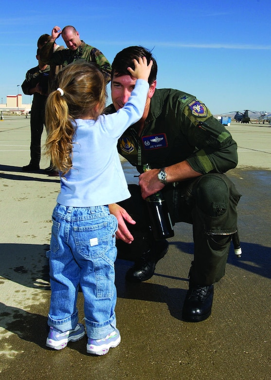 Col. Joe Lanni, then 412th Test Wing commander, smiles as his daughter, Michaela, 2, fixes his hair after being hosed down following his fini flight Jan. 31, 2006. Colonel Lanni passed command of the 412th TW to Col. Arnold Bunch on Feb. 2 in hangar 1600.  (Photo by Chad Bellay)