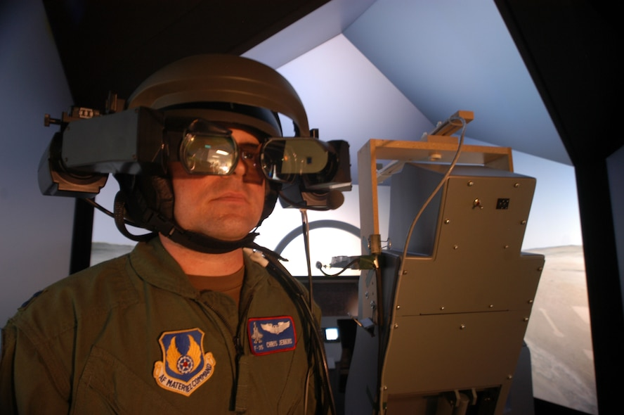 Capt. Chris Jenkins, Pilot Vehicle Interface lead for the F-35 Joint Strike Fighter Program Integrated Test Force, tries on the commercially available helmet-mounted display his team adapted for use with the JSF simulator. The team used the helmet for risk-reduction studies, which were completed June 20, 2006.  (Photo by Christopher Ball)