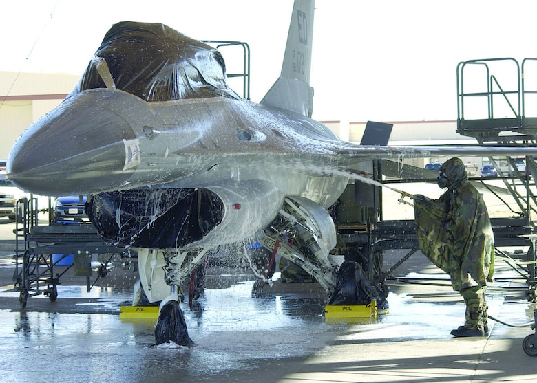 Members of the Joint Strike Fighter Integrated Test Force here prepare an F-16 for a final chemical decontamination test here Jan. 30, 2006. The F-16, used in place of an F-35, was sprayed with a chemical simulant, washed, then towed into a hangar and heated from 165- to 185-degree temperatures to accelerate the weathering of the remaining chemical. The goal of the testing is to decontaminate an entire aircraft to quickly return it to service should it be exposed to a chemical or biological agent. (Photo by Mark McCoy)