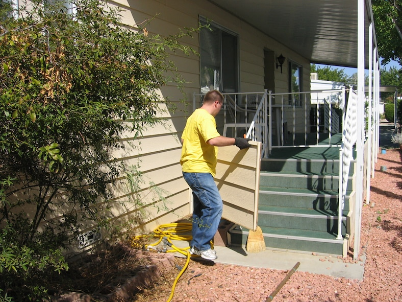 Airman 1st Class Jonathan Tuck, 412th Maintenance Squadron missile maintenance crew member, removes and cleans vinyl siding to help senior citizens repair their homes in the local community.  (Photo by Staff Sgt. Jessie Gregorio)