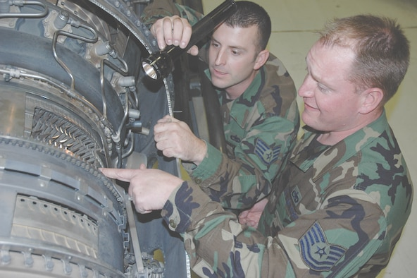 Tech. Sgt. Keith Hoffman, right, and Staff Sgt. Kevin Fogo, both with the 366th Maintenance Operations Squadron Maintenance Training Flight, look over the cutaway version of an F100 fighter engine to prepare for an upcoming class. Instead of using two-dimensional drawings of jet engines, the training organization uses the full-scale engine to improve the quality of their lessons by giving students more hands-on experience. Wing maintenance officials lauded the cutaway engine idea as one of its top innovations presented to Air Combat Command inspectors Nov. 15 as part of the command's annual Daedalian maintenance competition. (U.S. Air Force photo by Master Sgt. Brian Orban)
