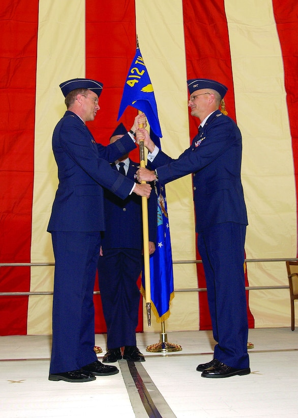 Maj. Gen. Curtis Bedke, Air Force Flight Test Center commander (left), hands the command flag to Col. Arnie Bunch, 412th Test Wing commander, during the test wing change of command ceremony here, Feb. 2, 2006.  (Photo by Chad Bellay)