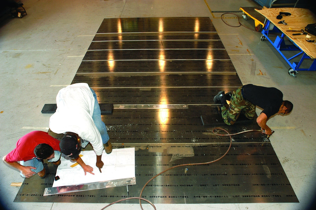 John Cracchiolo (left), Randy Morehead and Senior Airman Marlon Peeler, all structural maintenance craftsmen with the 412th Maintenance Squadron, assemble a ramp designed for C-5 landing gear tests scheduled for August 2006. The maintainers were tasked to build 16 ramps for low-speed taxi tests, and 20 for high-speed testing, and have used more than 200 sheets of aluminum, 300 sheets of plywood, 300 gallons of glue and thousands of fasteners putting the ramps together. (Photo by Christopher Ball)
