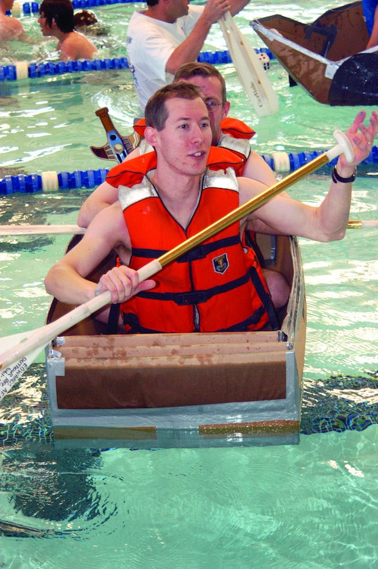 """Thr33 Ti3r Tug of Terror"" team members Brad DeVries and E.T. Waddell celebrate after finishing first place on the Build-a-Boat Competition race Feb. 11, 2006, at the Oasis Aquatic Center here. Build-a-boat is an annual event where competitors build a boat within two hours and then race it two-full lengths of an Olympic-size pool.  (Photo by Airman 1st Class Julius Delos Reyes)"