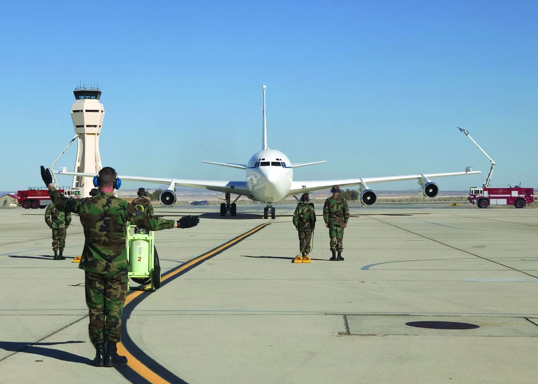 Crew members of the C-135C tail number 669, also known as Speckled Trout, watch the aircraft complete its fini-flight after taxiing underneath the fire department water cascade on Jan. 13, 2006.  (Photo by Bobbi Zapka)