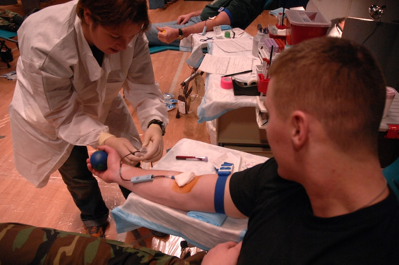 EIELSON AIR FORCE BASE, Alaska -- Susan Baker, manager, Blood Bank of Alaska Fairbanks Center, collects blood from Airman Kyle Kremer, 354th Medical Group, during the Blood Bank's mobile blood drive here on 21 Nov. The Blood Bank of Alaska supplies blood to military and civilian hospitals throughout Alaska. (U.S. Air Force Photo by Staff Sgt Joshua Strang)