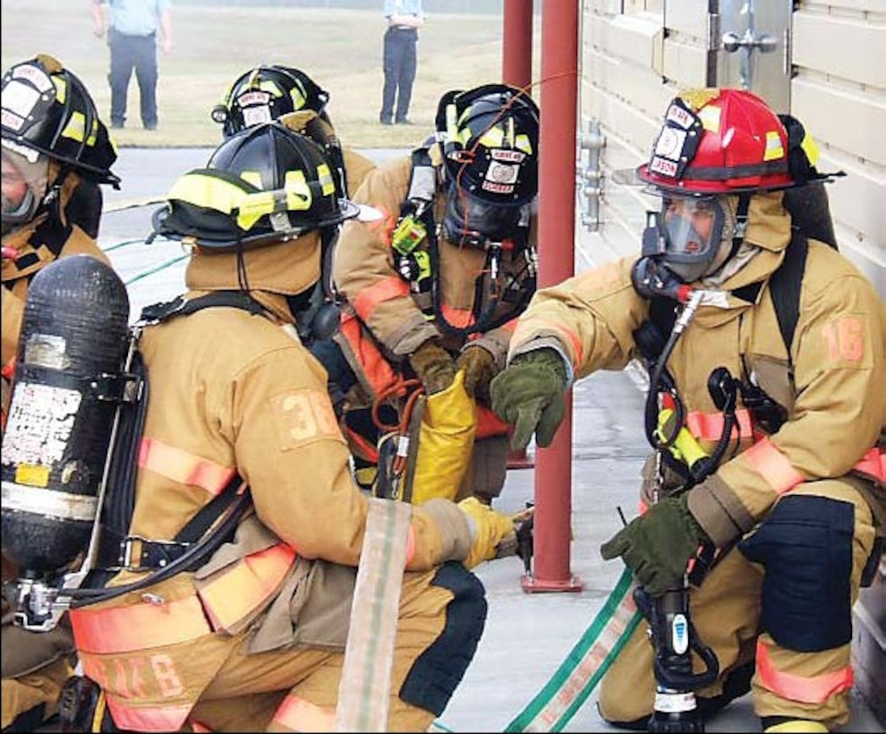 Robins firefighters prepare to enter their structural live fire trainer. Before making entry, the firefighters must conduct buddy checks to make sure everyone is geared up correctly.