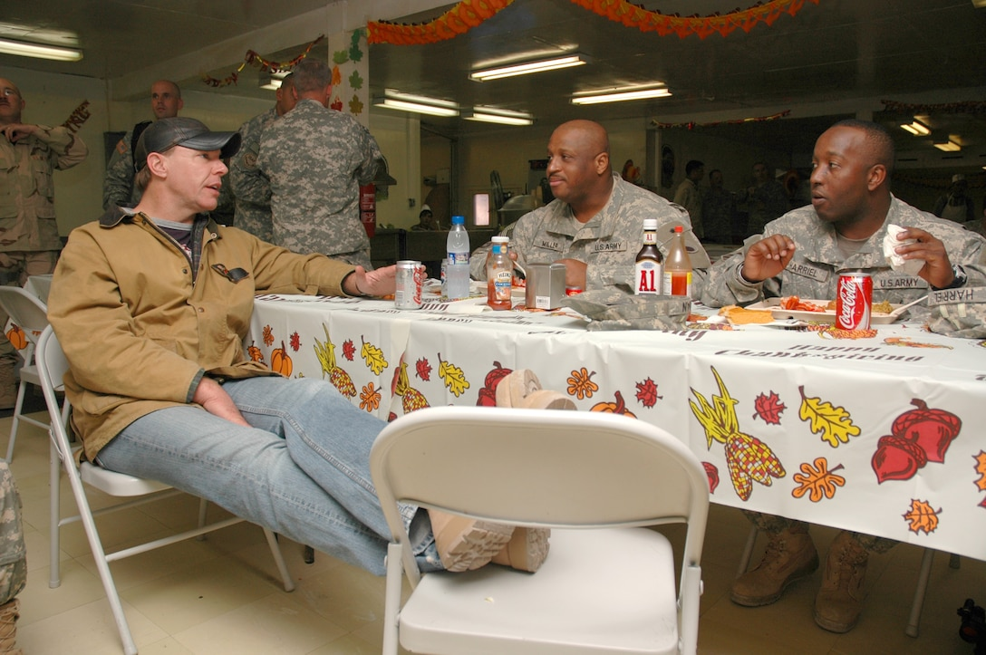 Country music singer Michael Peterson relaxes with soldiers on Forward Operating Base Ghazni, Afghanistan, on Thanksgiving Day. Through the USO, Peterson performed for troops and thanked them for their service and the sacrifices they are making.