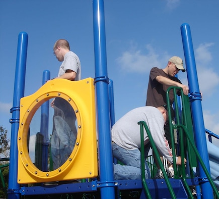 From left, Senior Airman Arron Eden, Tech. Sgt. Brian Yelton and Master Sgt. John Baliey put finishing touches on playground equipment at Gorenflo Elementary School in Biloxi. The trio and 17 other members of the 81st Training Support Squadron gave up their Nov. 11 for the humanitarian project. (U.S. Air Force photo by Maj. Paul Lips)