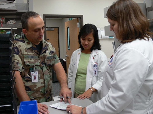 MOODY AIR FORCE BASE, Ga. -- Maj. (Dr.) Gabriel Florit, 23rd Medical Support Squadron pharmacy clinical coordinator here, talks with Quyen Cai, pharmacy drug information services intern, and Carla Barber, pharmacy adult medicine intern, about a patient's prescription. Moody's pharmacy is currently training four pharmacy students from the University of Florida's Doctorate of Pharmacy program. Moody also has a contract with the University of Georgia and Mercer University. (U.S. Air Force photo by Senior Airman Leticia Hopkins)