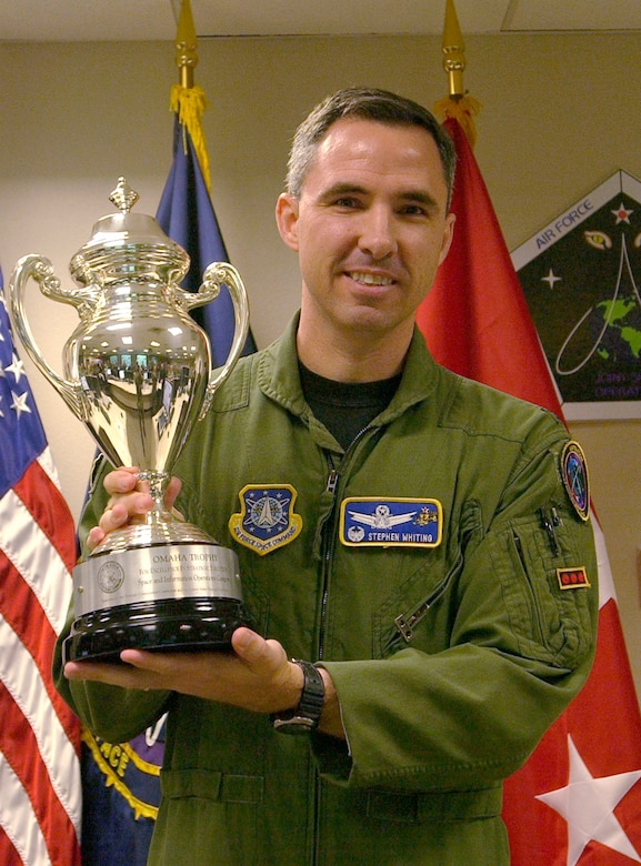 Col. Stephen Whiting, 614th Space Operations Group commander, displays the Omaha Trophy he and his team received for their outstanding performance. The award is presented annually to assigned units that demonstrate the highest standards of performance.  Selection for the award is based on formal evaluations, meritorious achievement, safety and other factors such as community involvement and humanitarian efforts. (U.S. Air Force photo by Airman Stephanie Longoria)
