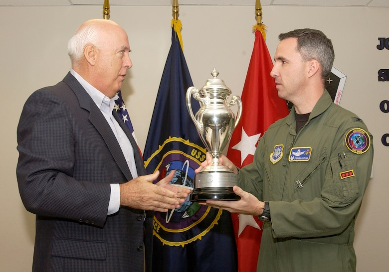 Ken Stinson, U.S. Strategic Command Consultation Committee chairman, presents the Omaha Trophy to Col. Stephen Whiting, 614th Space Operations Group commander, and his team for their outstanding performance. The award is presented annually to assigned units that demonstrate the highest standards of performance.  Selection for the award is based on formal evaluations, meritorious achievement, safety and other factors such as community involvement and humanitarian efforts. (U.S. Air Force photo by Airman Stephanie Longoria)