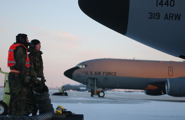 319th Aircraft Maintenance Squadron Airmen warm themselves by a heater on the flightline after fixing one of the jets Wednesday morning. Tuesday morning was the first significant snow fall of the winter with the coldest temperature so far this year. (photo/Airman 1st Class Ashley Coomes)