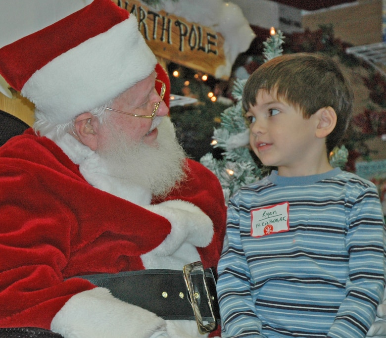 "EIELSON AIR FORCE BASE -- Ryan Lamoureux, son of Tech. Sgt. Grace Lamoureux, 354th Communications Squadron, informs Santa of his Christmas wishlist. Top on the list - ""Thomas the Train."" More than 30 children were selected for the first-ever Top of the World Toy Summit at the Santa Claus House in North Pole, Alaska. (U.S. Air Force photo by Senior Airman Justin Weaver)."