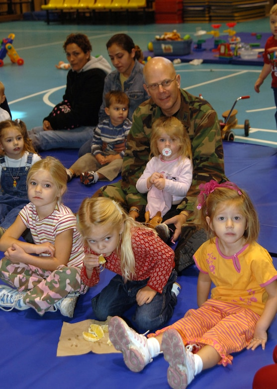 "Col. Murrell ""Tip"" Stinnette, (right) 39th Air Base Wing commander, prepares to sing songs with children of the preschool playgroup at the base Yout.h Center, following a volunteer appreciation ceremony, Nov. 28. (U.S. Air Force photo by Airman Kelly L. LeGuillon)"
