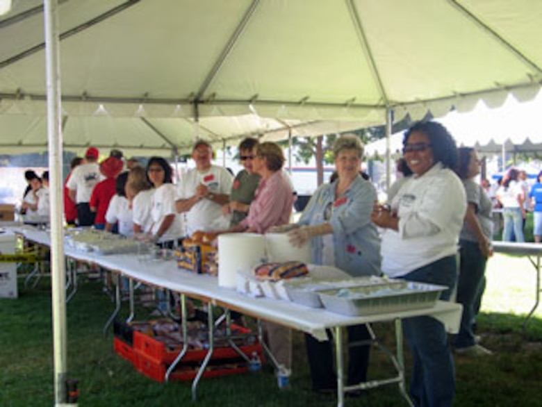Volunteers serve food during the annual base wide picnic held on Saturday, September 16. The local communities of Riverside and Moreno Valley organized and funded the picnic to show their appreciation to the military members who work at the base. More than 5,000 military members and their families attended the event. This is the 34th appreciate day picnic the community has hosted for March Air Reserve Base. (U.S. Air Force photo by MSgt Carson Hampton)