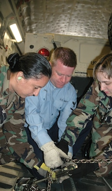 McCHORD AIR FORCE BASE, Wash., - Senior Airman Cheyenne Pantle (right) of the 86th Aerial Port Squadron, coaches Petty Officers 3rd Class Rosana Lima and Kurt Daubs in the proper use of tie downs to the floor of a C-17. This was the first time the Sailors had loaded cargo aboard a C-17. (USAF photo by Senior Airman Paul Haley)