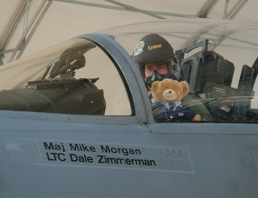"""Colonel Wilsbach, preps his wingman, """"Super Hero"""" for an F-15 sortie Wednesday morning.  The bear joined the wing Sept. 29 after Bailey Reese presented it to Colonel Wilsbach during the Celebrate Freedom ceremony at Longwood Elementary. (U.S. Air Force photo by Staff Sgt. Samuel King Jr.)"""
