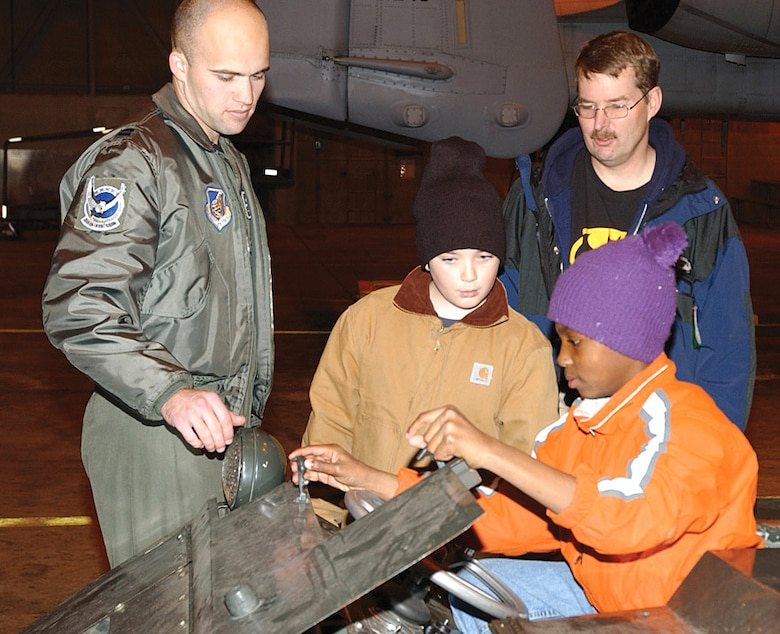 Capt. Travis Burton explains the functions of an MJ-1 vehicle used to load munitions onto aircraft Sept. 30 at Eielson Air Force Base, Alaska. The captain is a pilot with the 355th Fighter Squadron. (U.S. Air Force photo/Amn. Christopher Griffin)