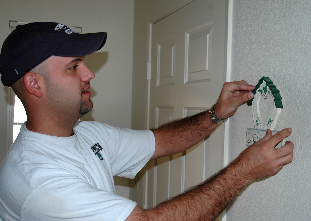 BUCKLEY AIR FORCE BASE, Colo. -- Staff Sgt. Josh Gordon, 460th Comptroller Squadron, hangs his welcome home key holder on the wall next to the front door in his new home at Buckley Air Force Base. Sergeant Gordon and his family are one of 14 families moving into family housing this week.  Phase one, which opened 28 units this week, has families moving through the end of October. Phase two has 32 units scheduled to open in November. Homes will be opening up in phases through April, with a total of 351 to be available. (U.S. Air Force photo by Staff Sgt. Sanjay Allen)