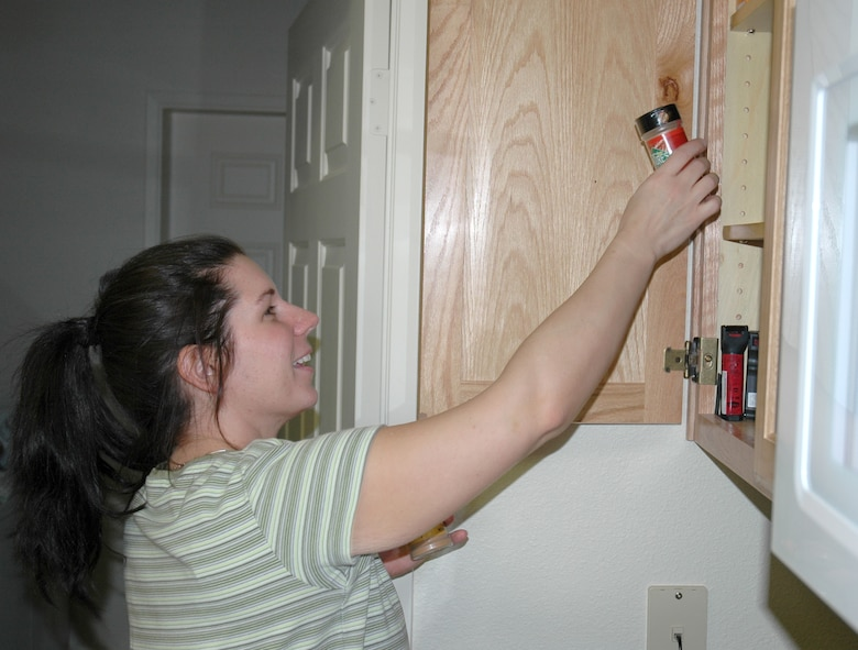 """BUCKLEY AIR FORCE BASE, Colo. -- Ms. Krista Gordon, wife of Staff Sgt. Josh Gordon's of the 460th Comptroller Squadron, puts spices away in the kitchen of their new home at Buckley Air Force Base. Sergeant Gordon and his family are one of 14 families moving into family housing this week.  """"We like it,"""" she said. """"The kids love it. Mya (their 3-year-old daughter) doesn't want to go back to the apartment.""""Phase one, which opened 28 units this week, has families moving through the end of October. Phase two has 32 units scheduled to open in November. Homes will be opening up in phases through April, with a total of 351 to be available. (U.S. Air Force photo by Staff Sgt. Sanjay Allen)"""
