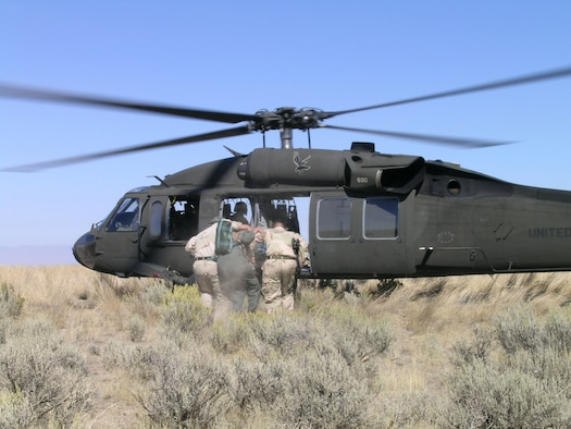 Survival, Evasion, Resistance and Escape specialists assist a simulated downed aircrew into a Black Hawk helicopter during Combat Survival Training near Mountain Home Air Force Base. (Courtesy photo)