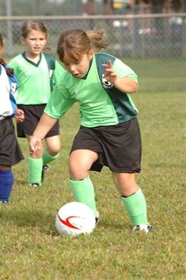 Ashley Knight, daughter of Staff Sgt. Robert and Kelly Knight, dribbles the ball downfield in a Seymour Johnson youth soccer game Saturday. (Photo by Tech. Sgt. Charles Tubbs)