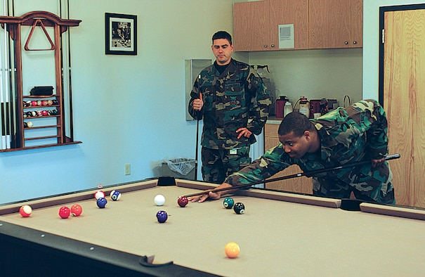 Senior Airmen Travis Paxton (left) and Garcia Tarver, both firefighters from the 4th Civil Engineer Squadron, play pool in the recreation room at the new fire station here Monday. The new station's amenities make life and work more bearable for the firefighters who are on duty for 24-hour shifts.  (Photo by Staff Sgt. Shawn J. Jones)