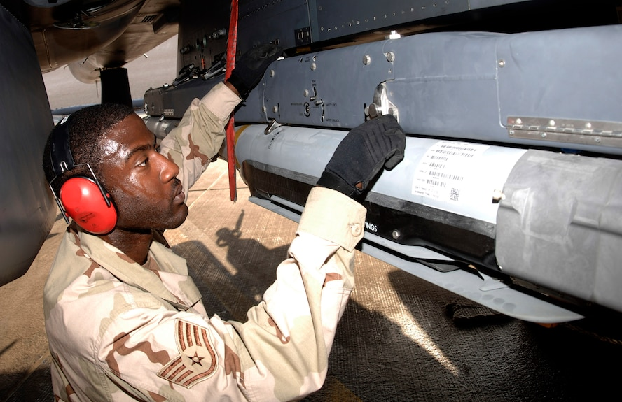 Staff Sgt. Kevin Harvey secures a weapons carriage with GBU-39/B small diameter bombs to an F-15E Strike Eagle. Sergeant Harvey is assigned to the 379th Expeditionary Aircraft Maintenance Squadron. (U.S. Air Force photo/Senior Airman Ricky Best)
