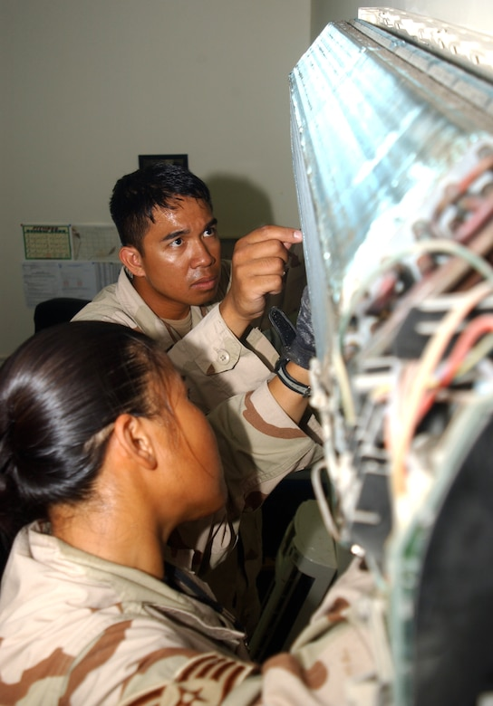 Senior Airman Ernesto Estalilla and Staff Sgt. Kathryn Santos repair a wall-mounted air-conditioning unit in the third-country national escort office at this deployed location in Southwest Asia Oct. 11. Both Airmen are part of a nine-person team that maintains better than 3,000 air conditioning units here for about 1,500 people and the 380th Air Expedtionary Wing. Both Airmen are assigned to the 380th Expeditionary Civil Engineer Squadron and deployed from Yokota Air Base, Japan. (U.S. Air Force photo/Master Sgt. Jason Tudor)