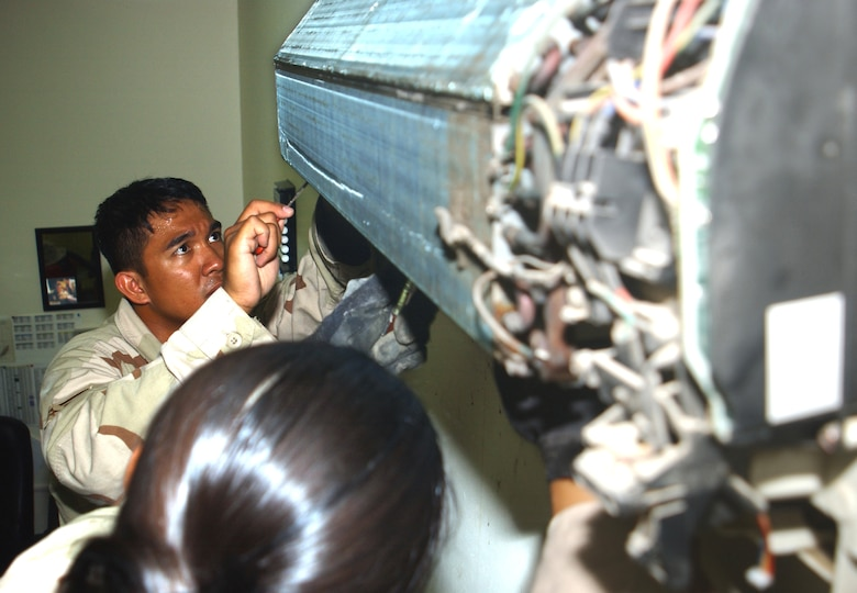 Senior Airman Ernesto Estalilla repairs a wall-mounted air conditioning unit in the third-country national escort office of at this deployed location in Southwest Asia Oct. 11. Airman Estalilla is part of a nine-person team that maintains better than 3,000 air-conditioning units here for about 1,500 people and the 380th Air Expedtionary Wing. He is assigned to the 380th Expeditionary Civil Engineer Squadron and deployed from Yokota Air Base, Japan. (U.S. Air Force photo/Master Sgt. Jason Tudor)