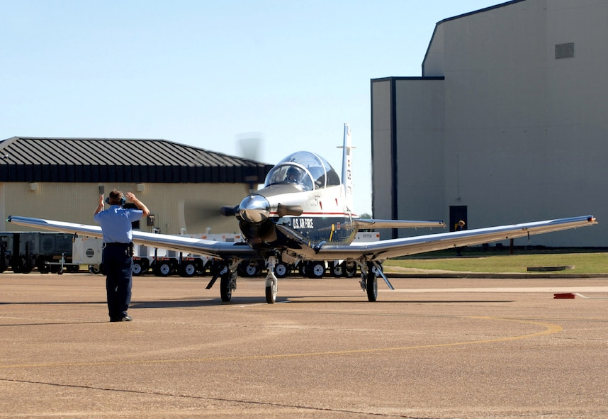 Lt. Col. Todd White taxis in with the first T-6 Texan assigned to the fleet at Columbus Air Force Base, Miss., fleet before presenting Col. Eric Theisen with the keys to the aircraft. Colonel White is the 41st Flying Training Squadron commander, and Colonel Theisen is the 14th Operations Group commander at Columbus AFB. (U.S. Air Force photo/Senior Airman Cecilia Rodriguez)