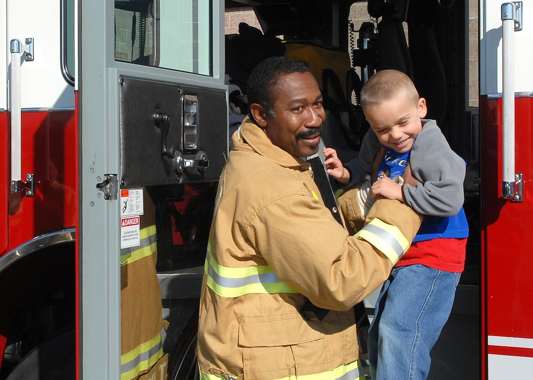 BUCKLEY AIR FORCE BASE, Colo. -- Fire Fighter Thomas Bryant lowers three-year-old Davian Mora from a firetruck during the fire department's visit with their mascot, Sparky the Fire Dog, to the Child Development Center here Oct. 12. The visit was to inform children about fire saftey and show them their equipment. Visiting the CDC was one of the events planed for Fire Prevention Week on the base. (U.S photo by Senior Airman Steve Czyz)