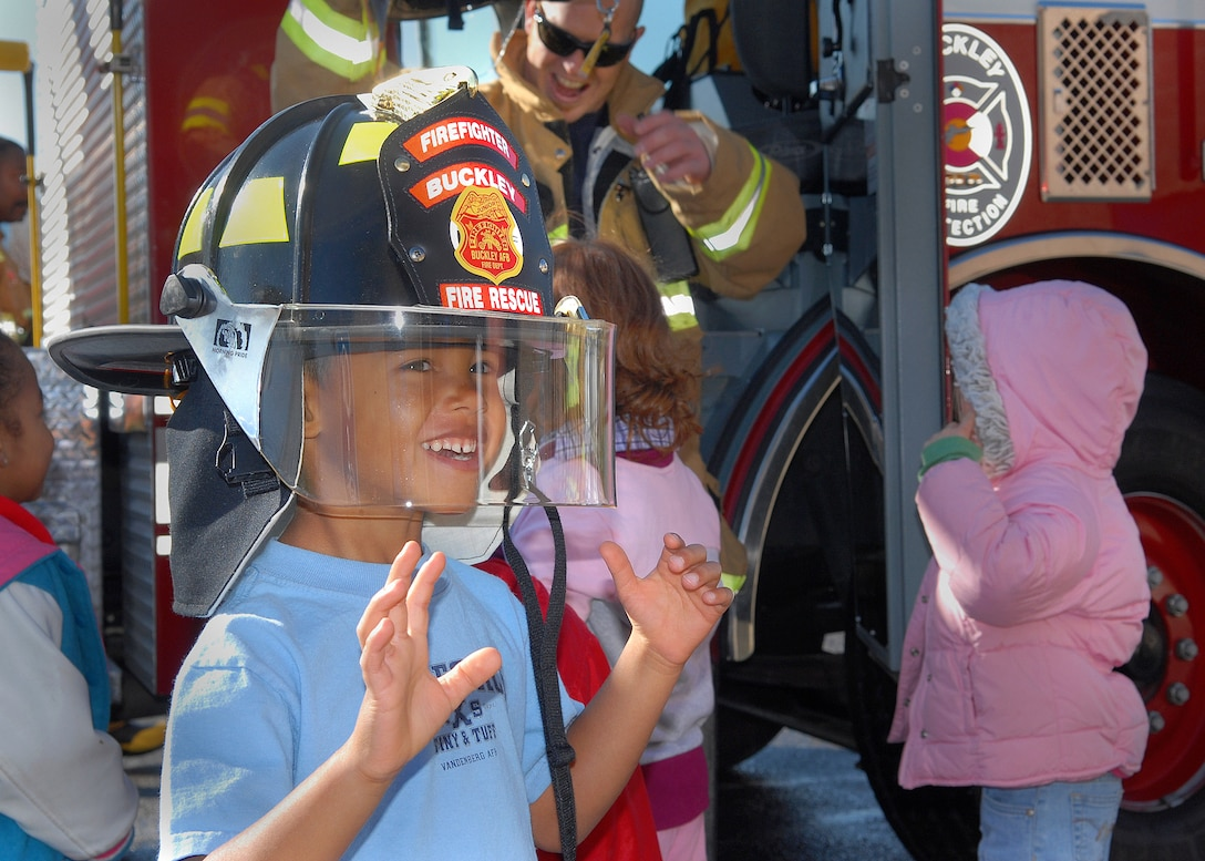 BUCKLEY AIR FORCE BASE, Colo. -- Four-year-old Jacob Wright tries on a hat belonging to one of base fire fighters during the fire department's visit with their mascot, Sparky the Fire Dog, to the Child Development Center here Oct. 12. The fire fighters visited the children to teach them about fire saftey and to show them their equipment. Visiting the CDC was one of the events planed for Fire Prevention Week on the base. (U.S. Air Force photo by Senior Airman Steve Czyz)