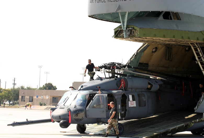 LAUGHLIN AIR FORCE BASE, Texas (AETCNS) -- Members of the 920th Rescue Wing from Patrick Air Force Base, Fla., unload one of three HH-60 Pave Hawk helicopters at Laughlin AFB, Texas. A C-5 Galaxy crew from Westover Air Reserve Base, Mass., delivered members of the search and rescue wing to Laughlin to pre-position the helicopters in response to Hurricane Rita, which is expected to hit landfall this weekend. Two additional Pave Hawks from Davis-Monthan Air Force Base, Ariz., flew to Laughlin Sept. 22 to support hurricane relief efforts. (U.S. Air Force photo by Master Sgt. Anthony Hill)