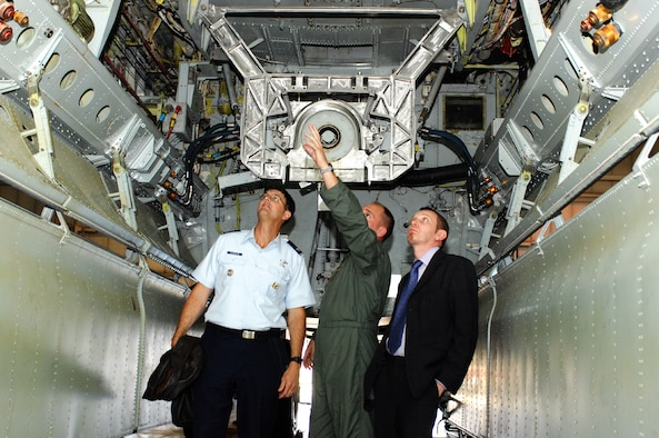 First Lt. Aaron Cook, 23rd Bomb Squadron, (middle), explains the inside of the payload bay of a B-52H Stratofortress, to Col. Steve Chabolla, Office of the Secretary of Defense Policy, and Nigel Basing, British Ministry of Defence, during a delegation visit here Oct. 5.
