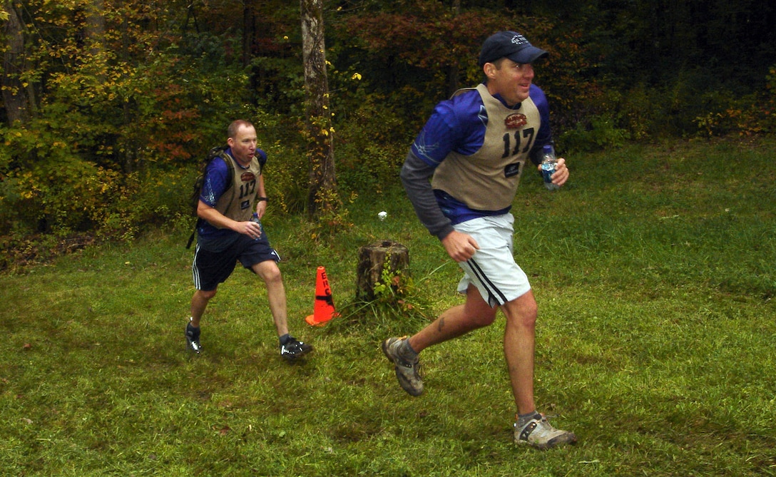 Mike Sonderman and Gene Vesey, members of the Defense Finance Accounting Service and 460th Comptroller Squadron Wilderness Challenge team, DFASt, run the last 200 yards of the 53-mile, six-event military adventure race Oct. 7. DFASt came in first out of five Air Force teams and 16th out of all 51 teams.